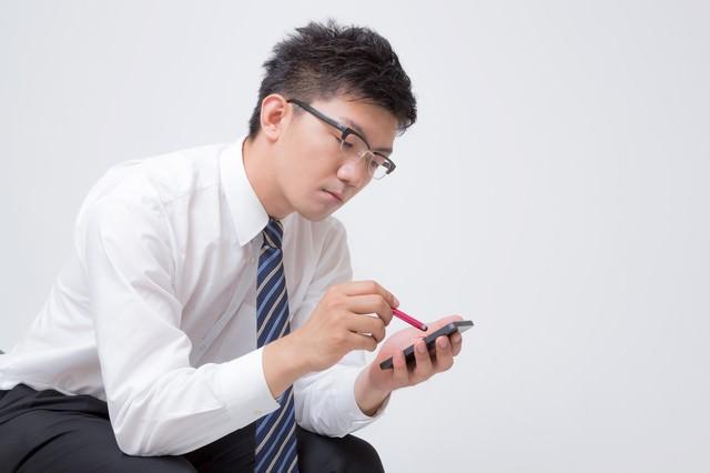スタライスペンでスマートフォンをいじる男性の写真