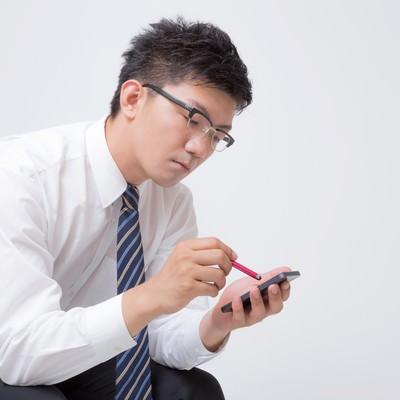 「スタライスペンでスマートフォンをいじる男性」の写真素材