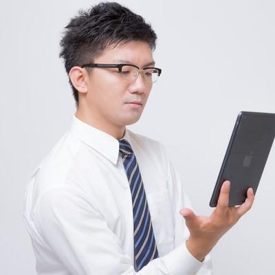 iPad mini で電子書籍を読むビジネスマンの写真