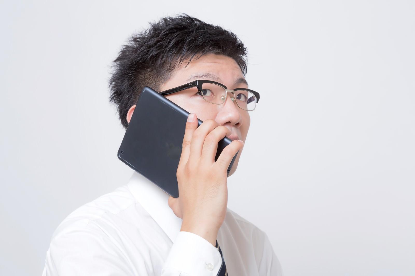 「iPad mini を電話機として使うサラリーマン」の写真[モデル:OZPA]