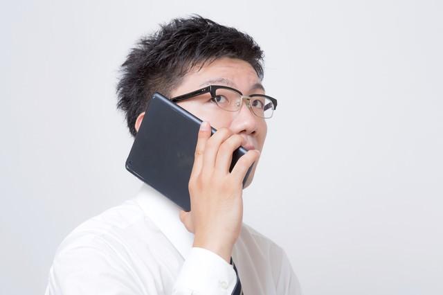 iPad mini を電話機として使うサラリーマンの写真
