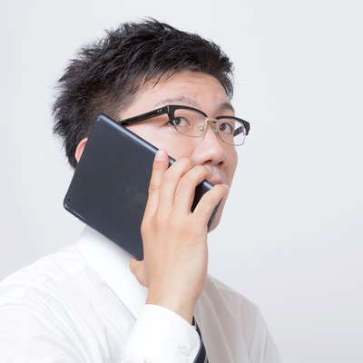 「iPad mini を電話機として使うサラリーマン」の写真素材