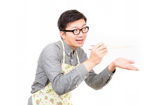 菜箸で「あーん」っと味見させる新婚の男性の写真