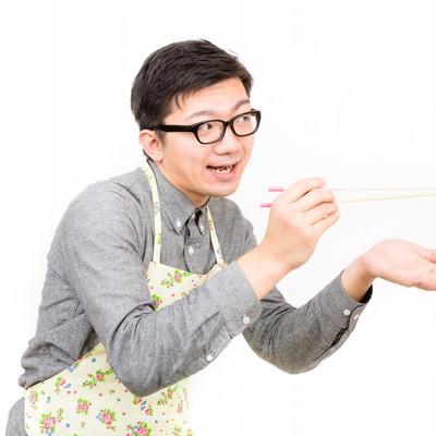 「菜箸で「あーん」っと味見させる新婚の男性」の写真素材