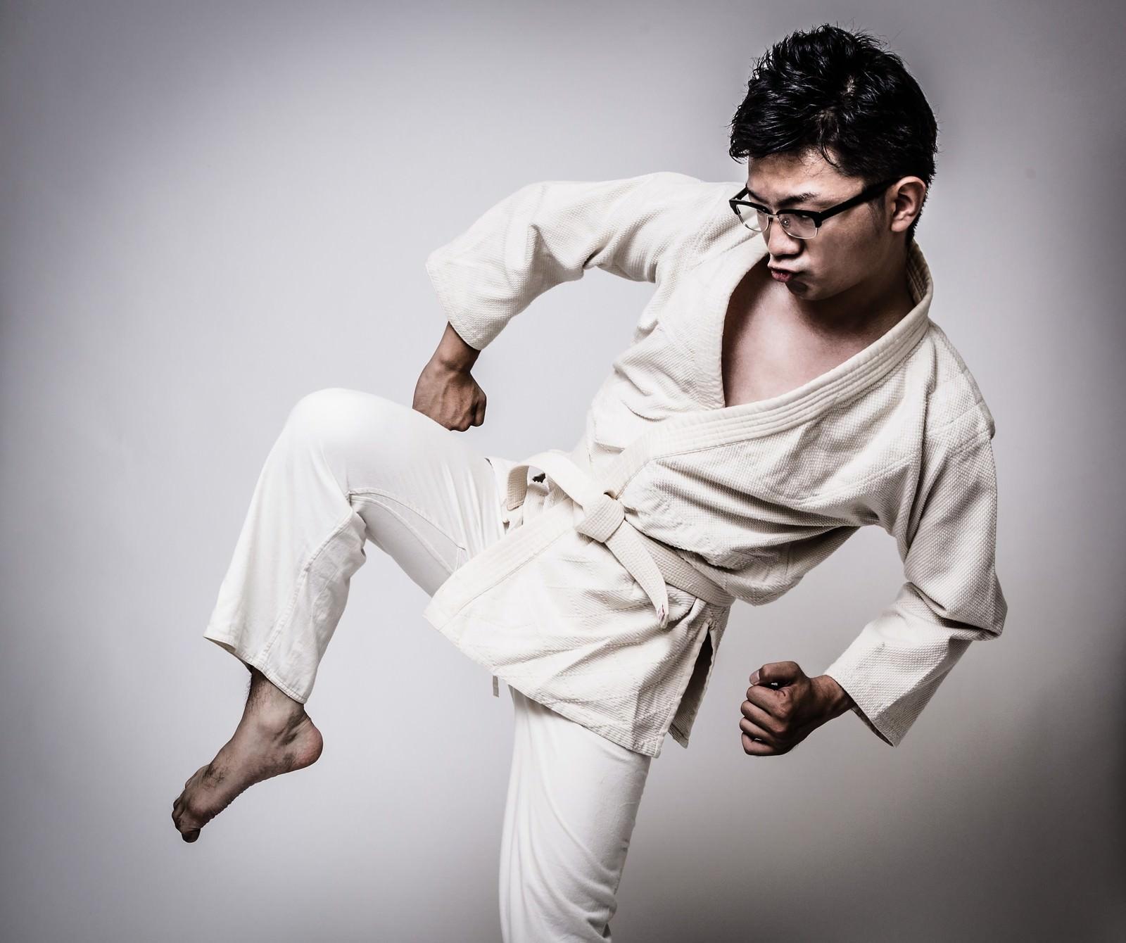 「膝蹴りをきめる白帯の男性」の写真[モデル:OZPA]