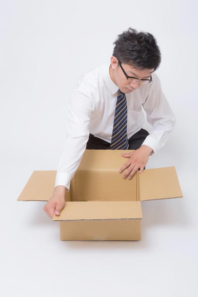 ダンボールを丁寧に開封するビジネスマンの写真