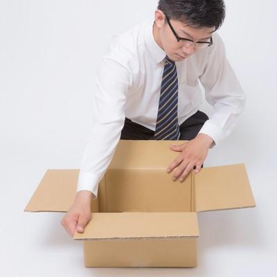 「ダンボールを丁寧に開封するビジネスマン」の写真素材