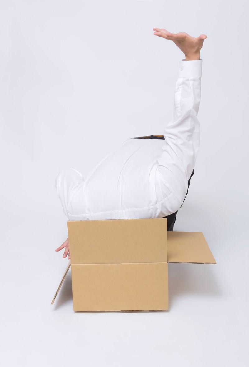 「開封したダンボールに吸い込まれてしまう男性」の写真[モデル:OZPA]