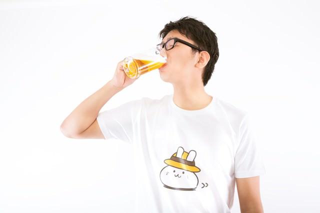 余裕でビールを飲み干す男性。ゴクゴクぷはー! おかわりの写真