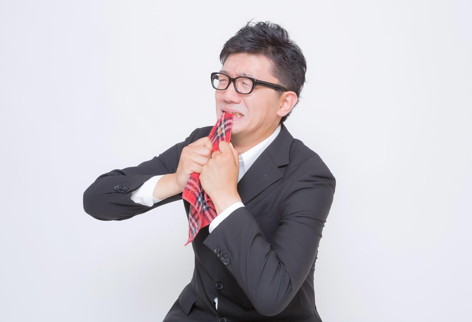 「ハンカチ噛んで全力で悔しがるサラリーマン」の写真[モデル:OZPA]