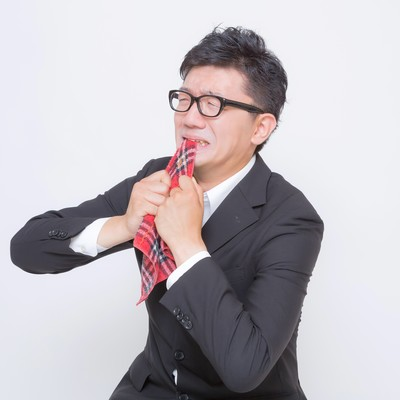 「ハンカチ噛んで全力で悔しがるサラリーマン」の写真素材