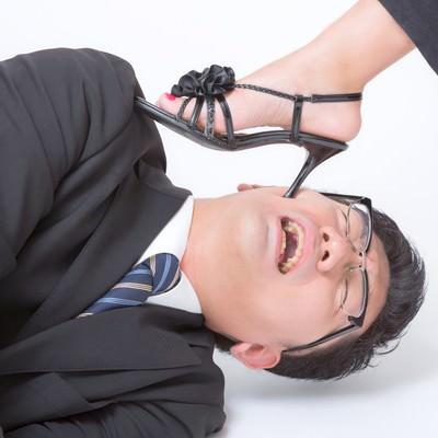 「ピンヒールでお仕置きされるスーツ姿の男性」の写真素材