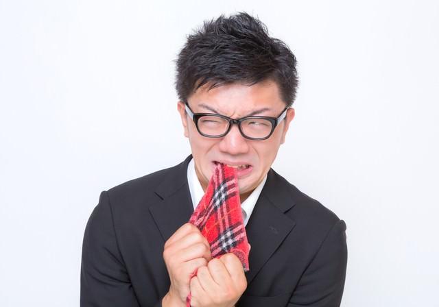 悔しくてハンカチを噛む眼鏡男子の写真