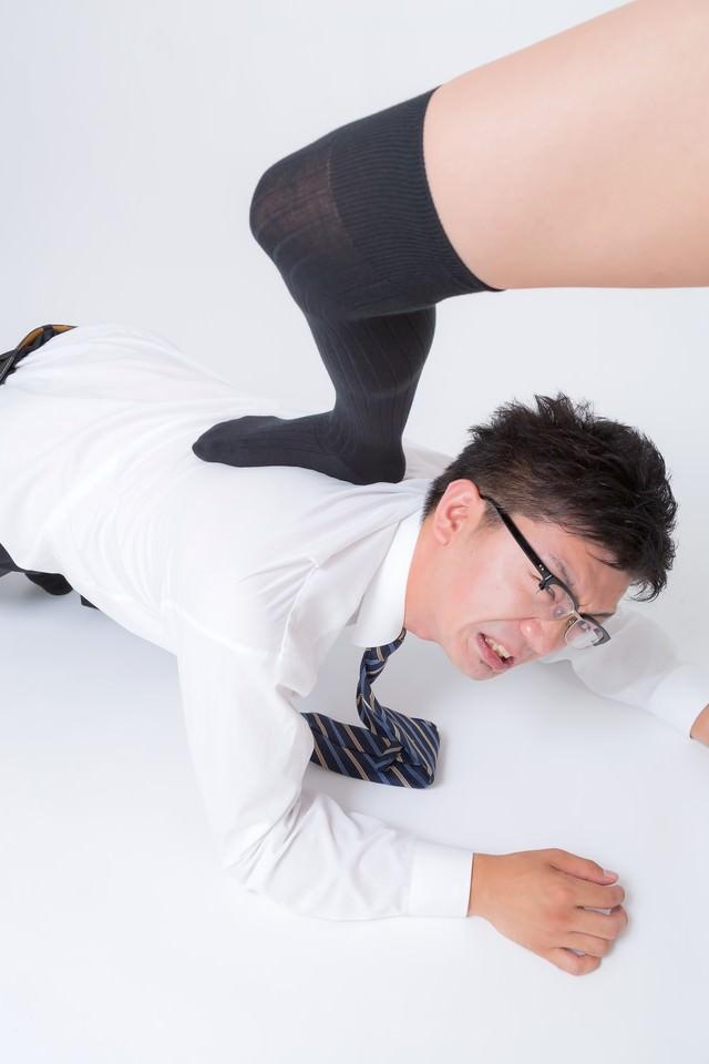 四つん這いで足蹴にされるスーツ姿の男性の写真