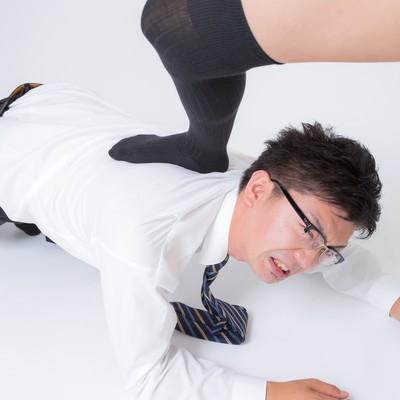 「四つん這いで足蹴にされるスーツ姿の男性」の写真素材