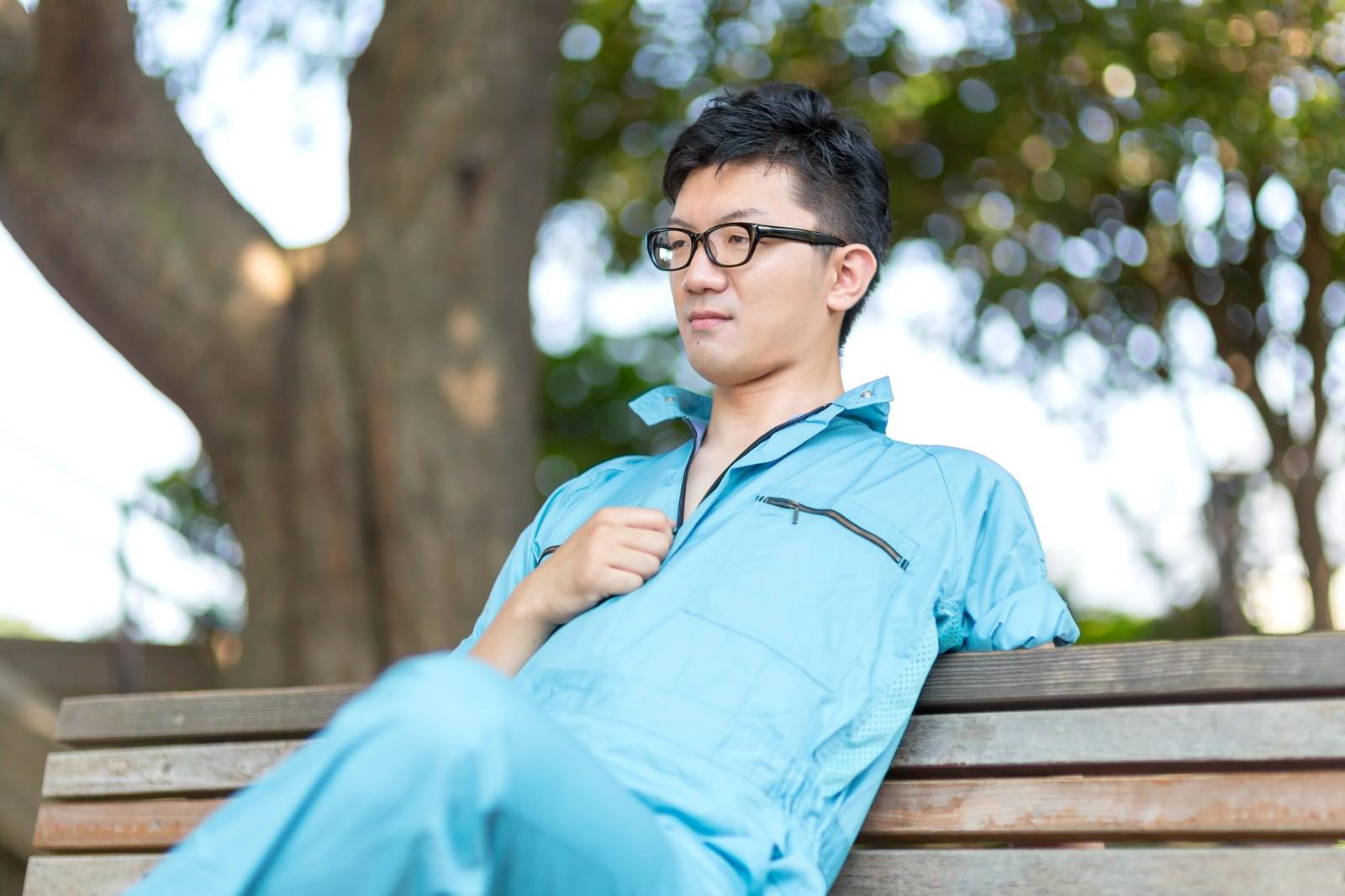 「公園のベンチで休憩する、やる気満々な作業員」の写真[モデル:OZPA]