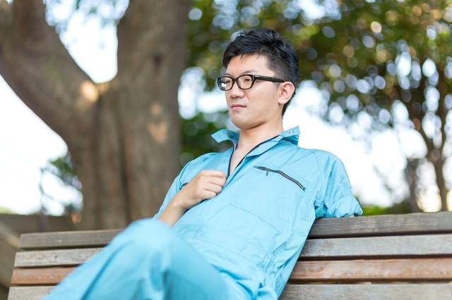 公園のベンチで休憩する、やる気満々な作業員の写真