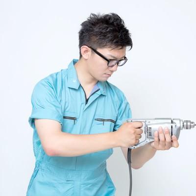 電気ドリルを構える現場作業員の写真