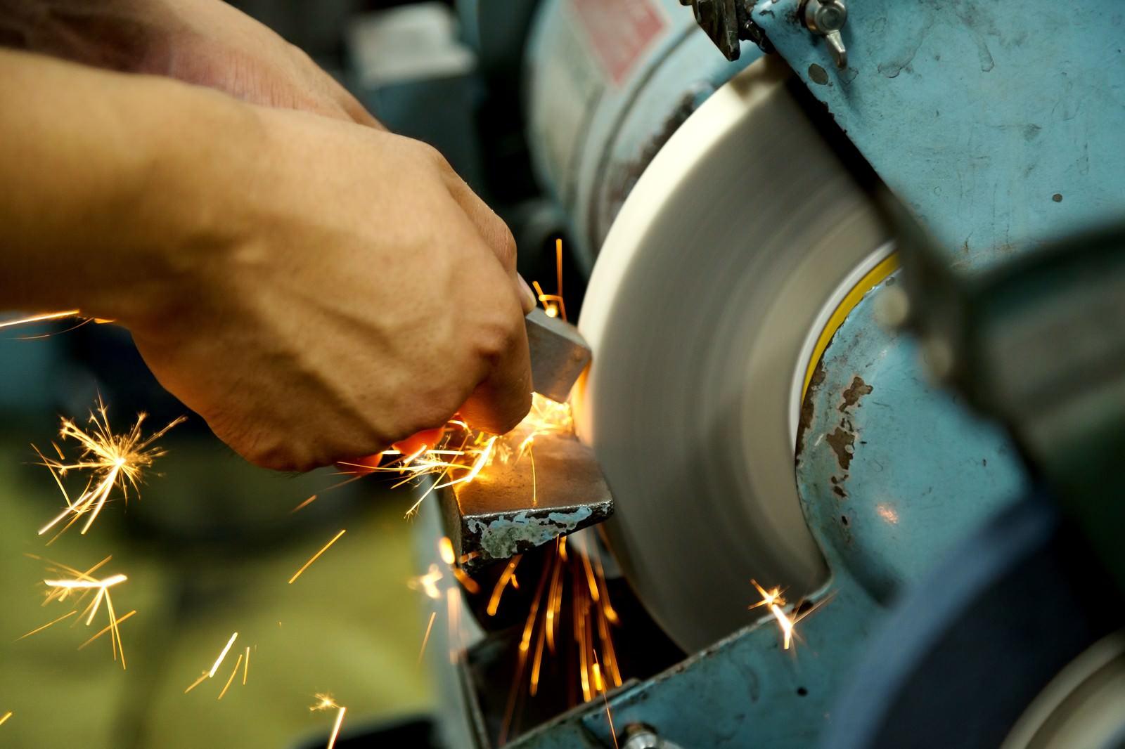 「グラインダーを使う職人の手と火花が散る様子グラインダーを使う職人の手と火花が散る様子」のフリー写真素材を拡大