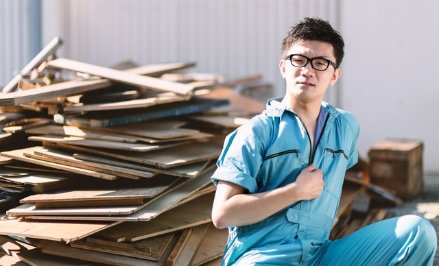 廃材置き場にいた青い作業着姿の男性の写真