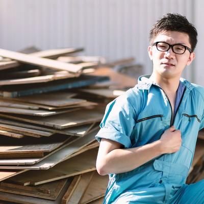 「廃材置き場にいた青い作業着姿の男性」の写真素材