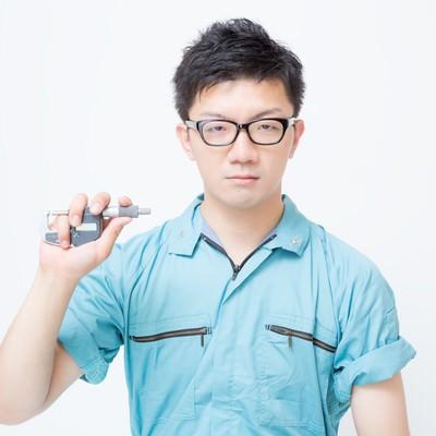 マイクロメーターを持つ作業員の写真
