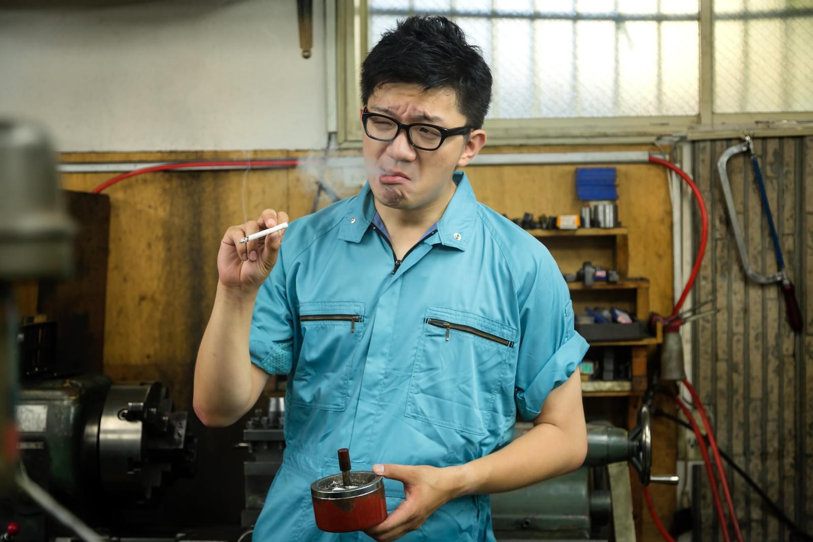 「納期に追われた仕事が終わり、タバコで一服中の作業員」の写真[モデル:OZPA]