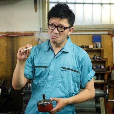 「納期に追われた仕事が終わり、タバコで一服中の作業員」の写真素材