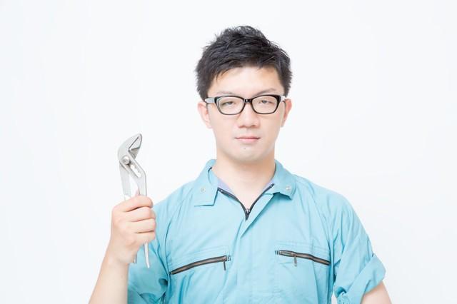 プライヤーを片手に持った作業着姿の男性の写真