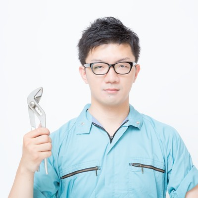 「プライヤーを片手に持った作業着姿の男性」の写真素材