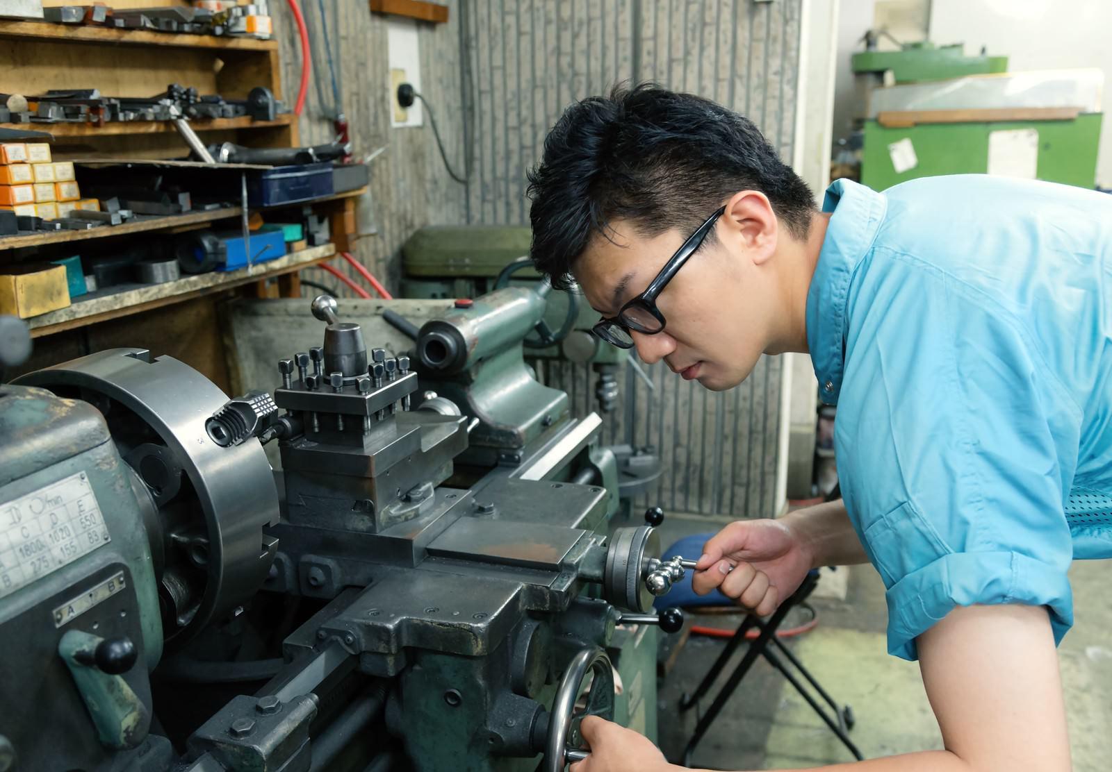「汎用旋盤で中グリ用刃物の芯高を確認し、ハンドルで調整中の男性 | ぱくたそフリー素材」の写真[モデル:OZPA]