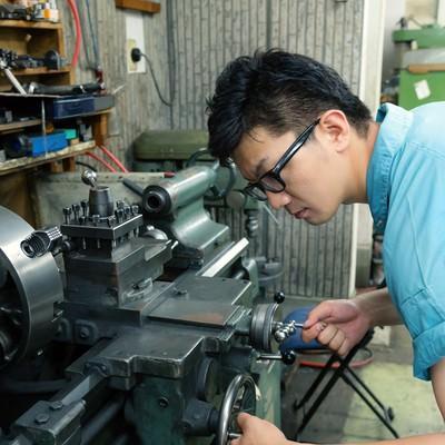 「汎用旋盤で中グリ用刃物の芯高を確認し、ハンドルで調整中の男性」の写真素材