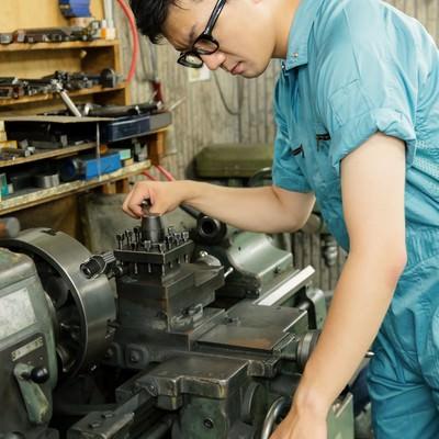 汎用旋盤のバイトホルダーを締める男性の写真