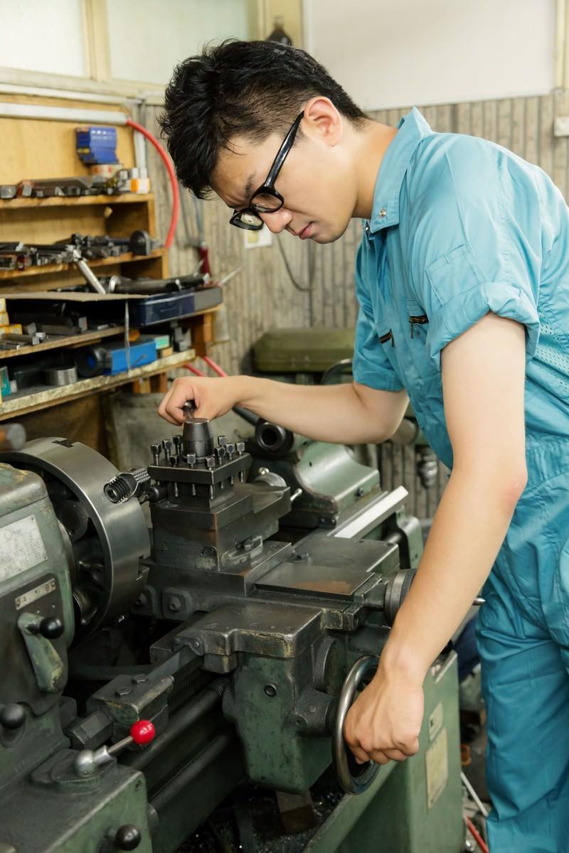 「汎用旋盤のバイトホルダーを締める男性」の写真[モデル:OZPA]