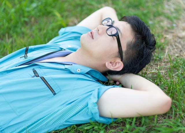 休憩中、芝生で空を眺める青い作業着姿の男性の写真