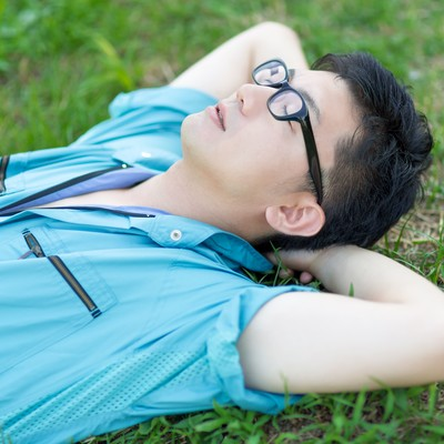 「休憩中、芝生で空を眺める青い作業着姿の男性」の写真素材
