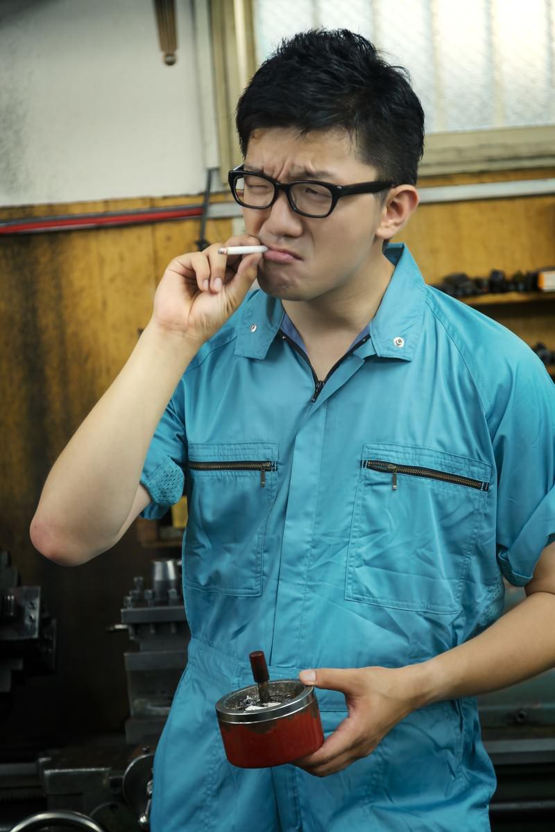 「工場で煙草を吸う男性」の写真[モデル:OZPA]