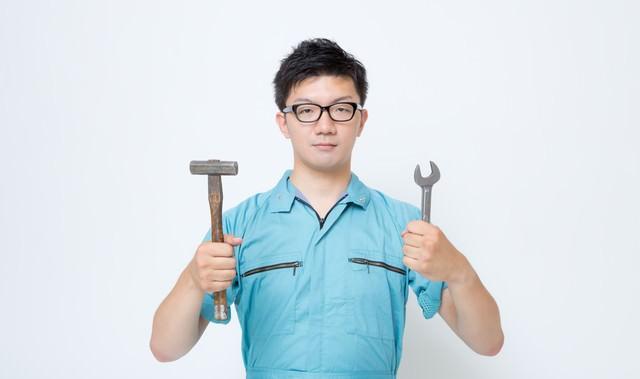 使い古したハンマーとスパナを両手に持つ作業着の男性の写真