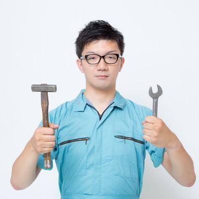 「使い古したハンマーとスパナを両手に持つ作業着の男性」の写真素材