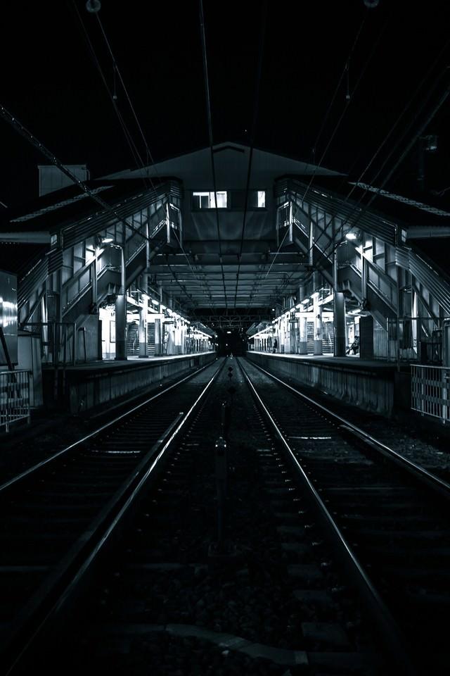 深夜のホームと線路の写真