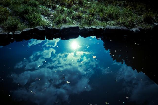 池に反射した雲と太陽の写真