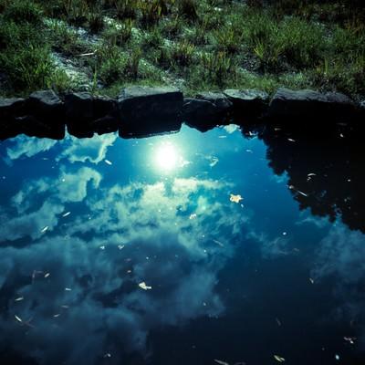 「池に反射した雲と太陽」の写真素材