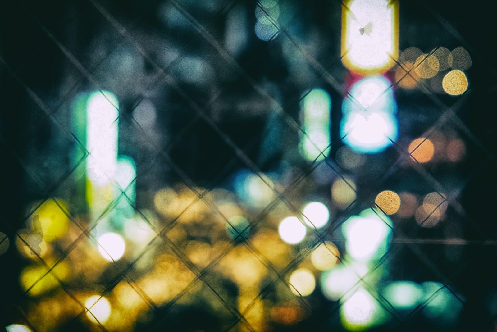 「フェンスとボケた繁華街フェンスとボケた繁華街」のフリー写真素材を拡大