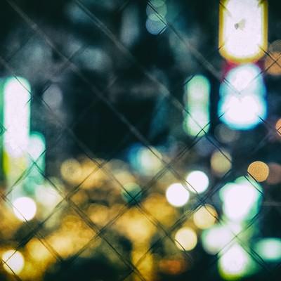 フェンスとボケた繁華街の写真