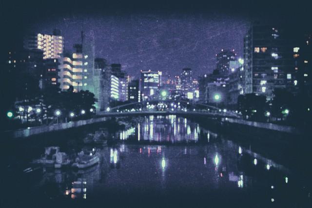 日も落ちた都会の河川(ノイズ)の写真