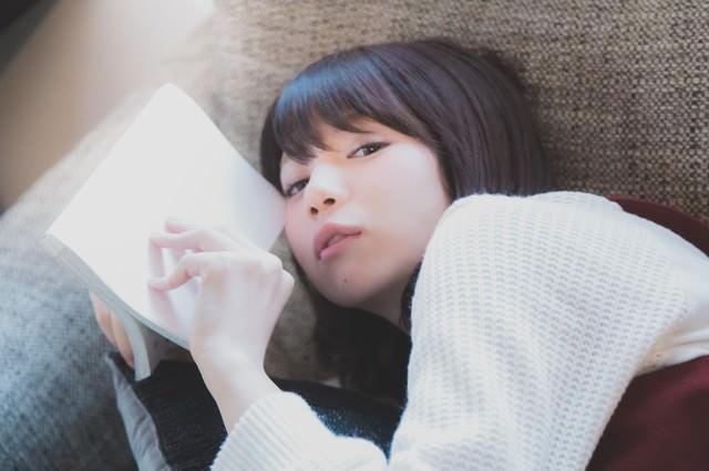 ソファーに寝転がりマンガを読む美女の写真