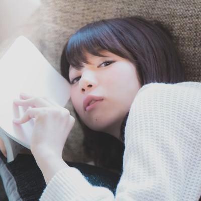 「ソファーに寝転がりマンガを読む美女」の写真素材