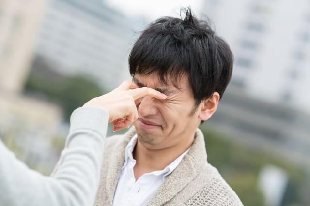 恋人との喧嘩で目を潰される男性の写真