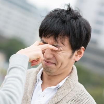 「恋人との喧嘩で目を潰される男性」の写真素材