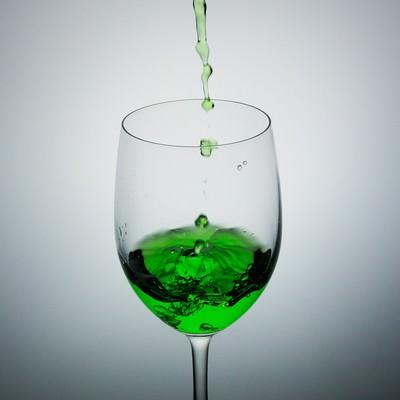 「グラスに入った緑色の液体」の写真素材